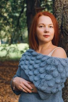Vrouw met rood haar en een gebreide trui staat bij een boom in het park in de stralen van de ondergaande zon