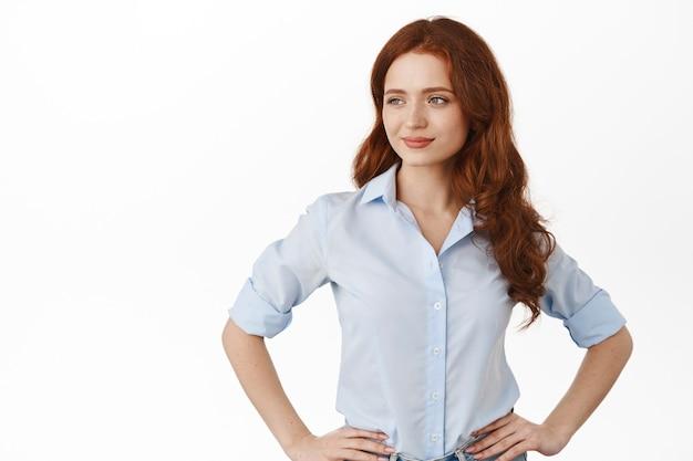 Vrouw met rood haar, hand in hand, tevreden en zelfverzekerd opzij kijkend, zaken doen, zelfverzekerd op wit staan