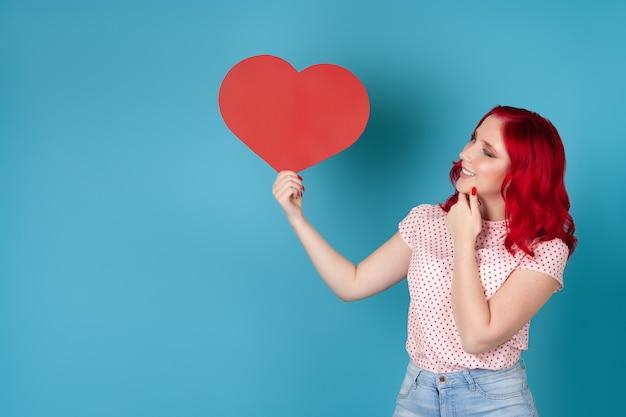 Vrouw met rood haar houdt een hart van rood papier vast en krabt met haar hand op haar kin