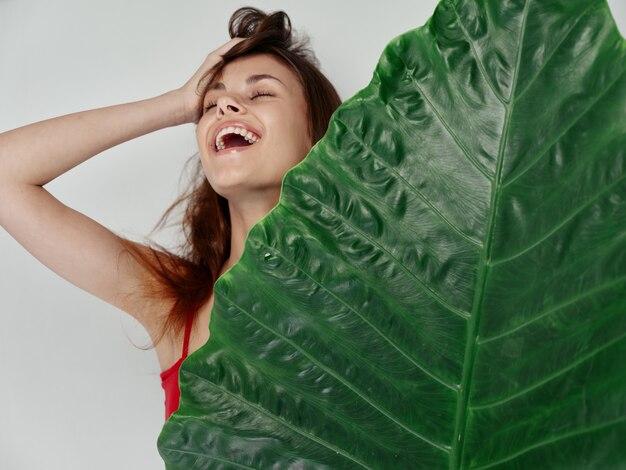 Vrouw met rood haar houdt groen palmblad in haar hand