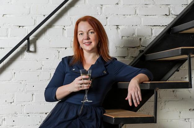 Vrouw met rood haar in donkerblauwe jurk met glas champagne, zittend op metalen ladder loft tegen witte bakstenen muur.