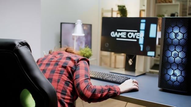 Vrouw met rood haar van streek dat ze verloor bij een online shooter-game zittend op een gamestoel met een koptelefoon op.