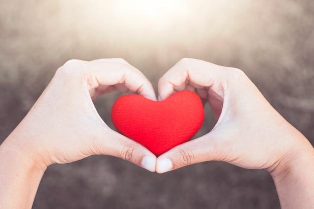 Vrouw met rood hart in handen en maak hand hart vorm