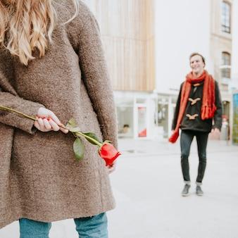 Vrouw met roos achter rug wachten op man