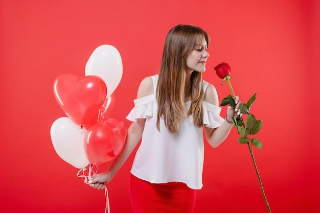 Vrouw met roos en kleurrijke hartvormige ballonnen geïsoleerd over rode muur