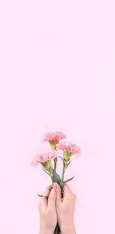 Vrouw met roze anjer over roze tafel achtergrond