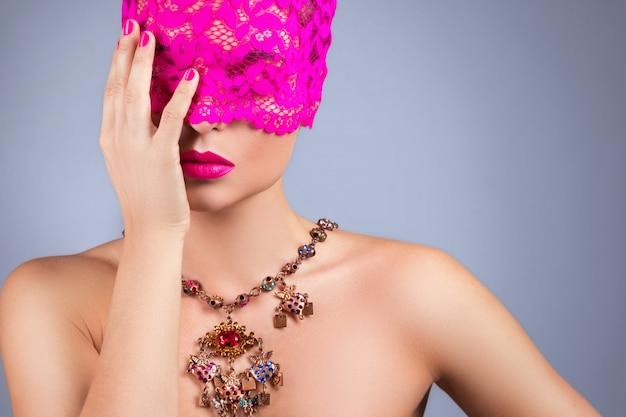 Vrouw met roze blinddoek op haar ogen