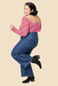 Vrouw met roze bovenkant en jeans plus groottemode