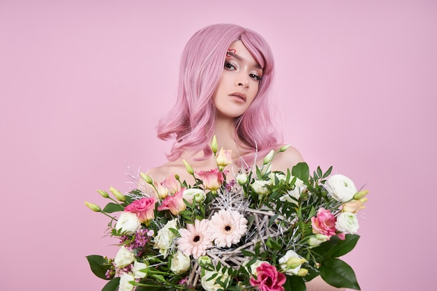Vrouw met roze de bloemboeket van de haarholding