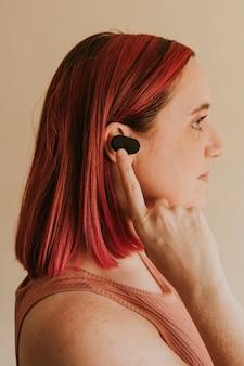 Vrouw met roze haar dat draadloze oordopjes draagt