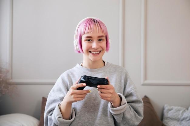 Vrouw met roze haar die een videogame speelt