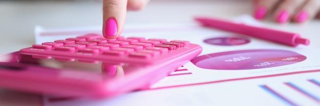 Vrouw met roze manicure rekenen op rekenmachine in de buurt van papier met grafieken closeup