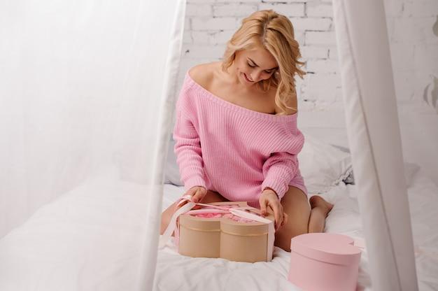 Vrouw met roze shirt zittend op het bed met de doos met roze bloemen
