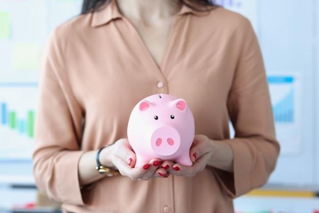 Vrouw met roze spaarvarken in kantoor close-up