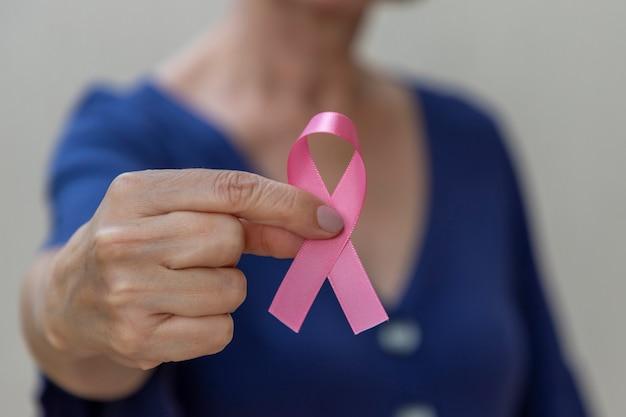 Vrouw met roze strik in haar hand. preventiecampagne tegen borstkanker. roze oktober