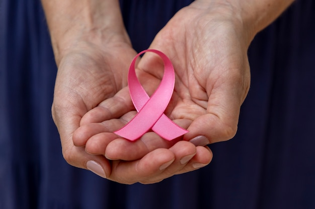 Vrouw met roze strik in handen. preventiecampagne tegen borstkanker. roze oktober