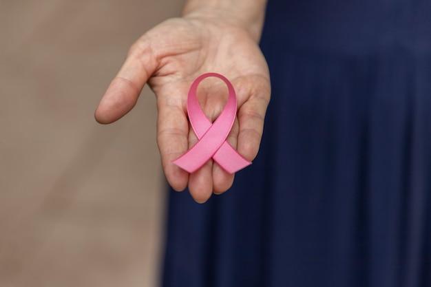 Vrouw met roze strik op haar handpalm. preventiecampagne tegen borstkanker. roze oktober