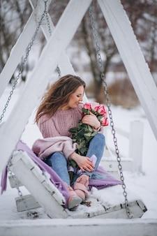 Vrouw met rozen buiten in de winter zittend op schommels