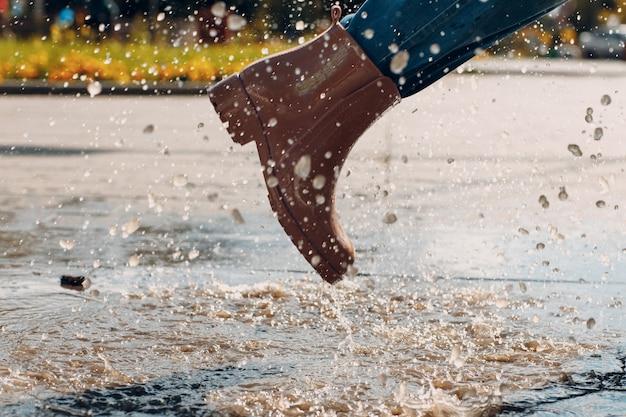 Vrouw met rubberen regenlaarzen die loopt en springt in een plas met waterspatten en druppels in de herfstregen
