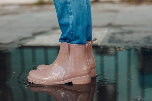 Vrouw met rubberen regenlaarzen die rennen en springen in de plas met waterplons en druppels in de herfstregen.