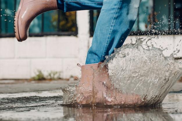 Vrouw met rubberen regenlaarzen die rennen en springen in de plas met waterplons en druppels ...
