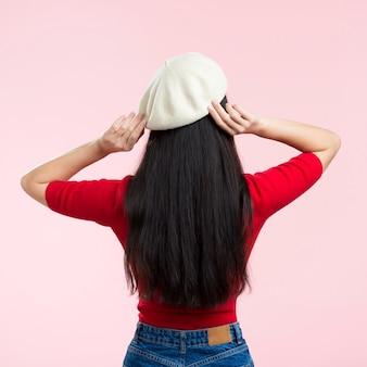 Vrouw met rug die haar hoed bevestigt