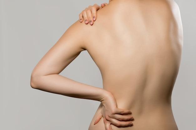 Vrouw met rugpijn geïsoleerd op een grijze achtergrond scoliose ruggenmergproblemen op de rug van de vrouw mooie naakte vrouw die haar rug aanraakt