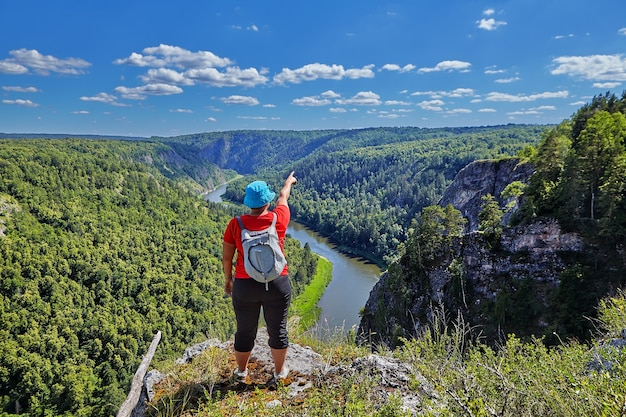 Vrouw met rugzak achter haar, gekleed in rode trui en blauwe hoed, wijst vinger naar deel van bos en rivier, ze staat op de rand van de bergtop op zonnige zomerdag.