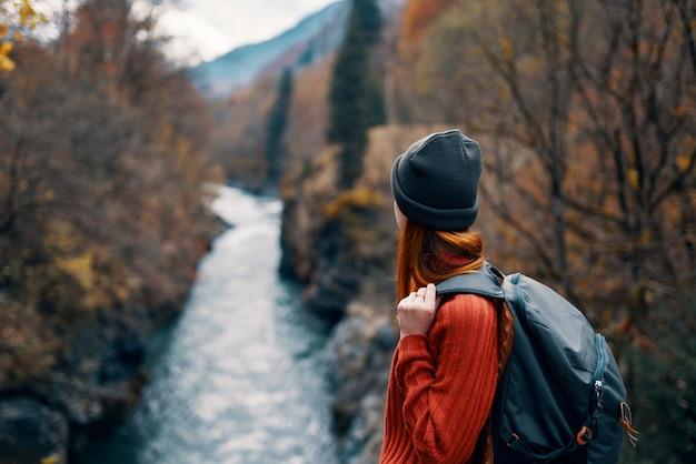 Vrouw met rugzak bewondert de rivier in de bergen, natuurreizen