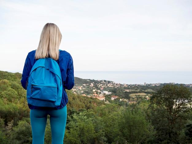 Vrouw met rugzak bovenop berg