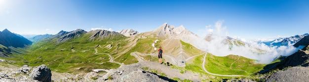 Vrouw met rugzak rusten op de bergtop, kijkend naar uitzicht dramatisch landschap vallei zomer activiteit fitness welzijn vrijheid concept, achteraanzicht