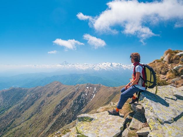 Vrouw met rugzak rusten op de bergtop, kijkend naar weergave dramatische landschap vallei zomeractiviteit