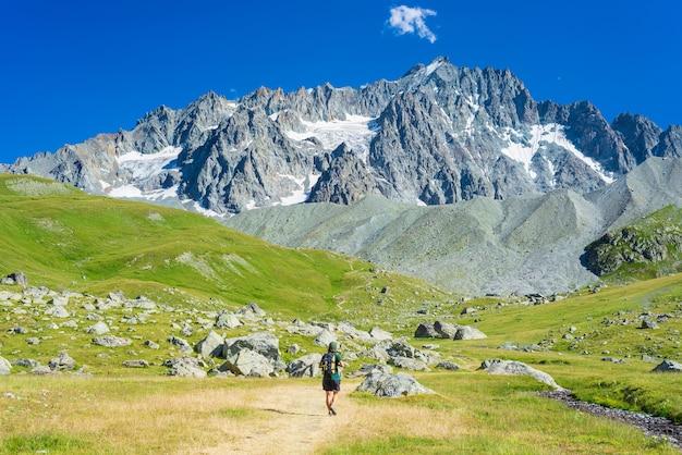 Vrouw met rugzak wandelen naar de bergtop, schilderachtige gletsjer en dramatische landschapszomer fitness
