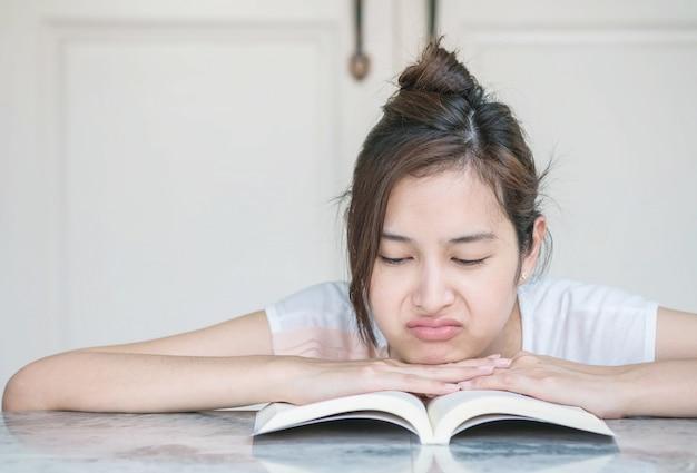 Vrouw met saai gezicht met een boek op marmeren tafel in de voorkant van het huis