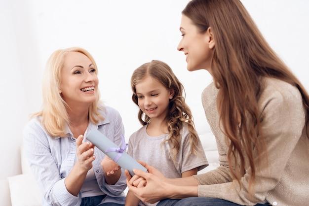 Vrouw met schattig klein meisje geeft volwassen vrouw certificaat.