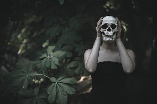 Vrouw met schedel in bos