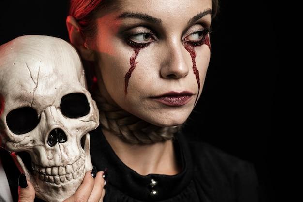 Vrouw met schedel op schouder