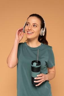 Vrouw met schildpadzak en hoofdtelefoons