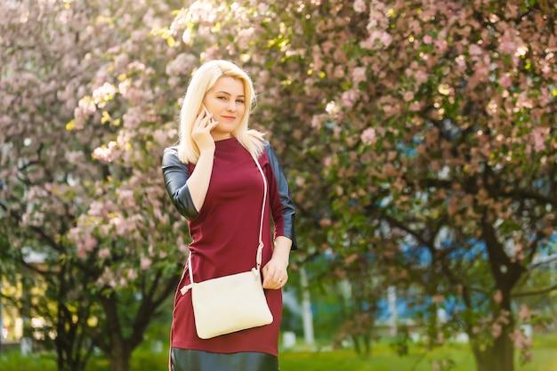 Vrouw met schitterende glimlach die pret in bloeiende tuin hebben.