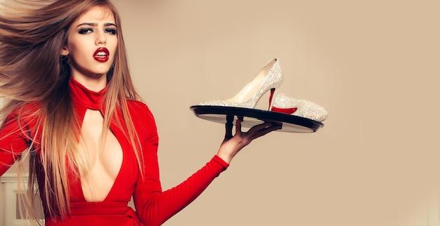 Vrouw met schoenen op dienblad glamour jonge vrouw in rode jurk met sprankelend paar elegante schoenen op dienblad ober hoge hakken concept
