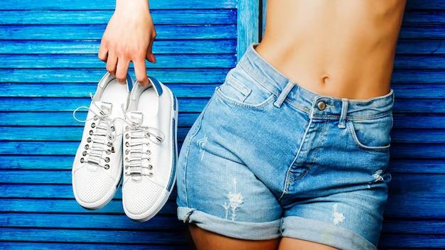 Vrouw met schoenen op een blauwe achtergrond. vrouw met een paar witte schoenen. meisje houdt een paar schoen vast. meisje met een mooie taille in jeansborrels. vrouw op een blauwe achtergrond met een platte buik.