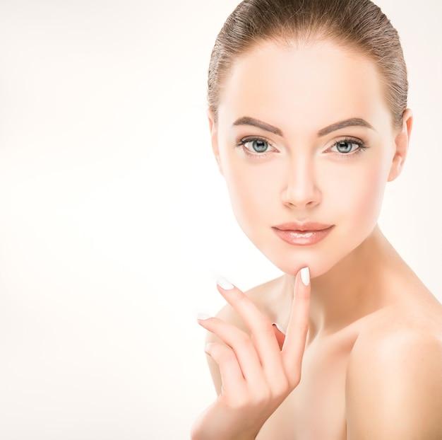 Vrouw met schone, frisse huid en lichte make-up raakt het gezicht aan met een slanke vinger met witte manicure
