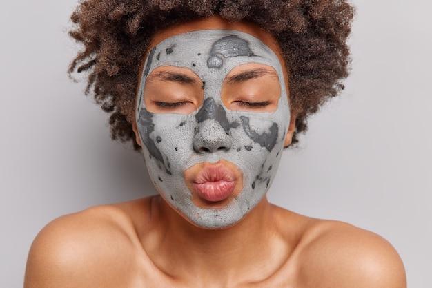 Vrouw met schone, gezonde huid naakt lichaam brengt voedend kleimasker op gezicht aan houdt lippen gevouwen ogen gesloten wacht op kus geïsoleerd op wit