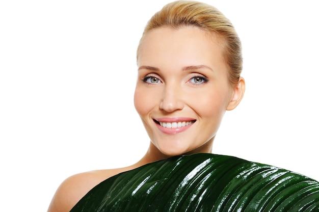 Vrouw met schone gezondheidshuid en vers blad die haar lichaam behandelen