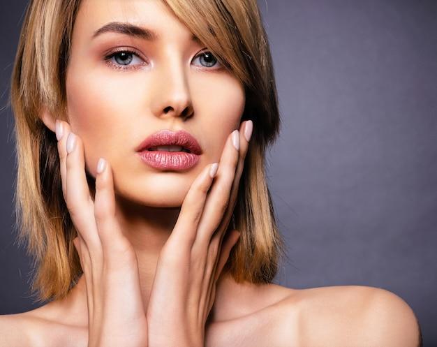 Vrouw met schoonheidsgezicht en schone huid. sexy blonde vrouw. aantrekkelijk blond model met blauwe ogen. mannequin met een rokerige make-up. closeup portret van een mooie vrouw. creatief kort kapsel.