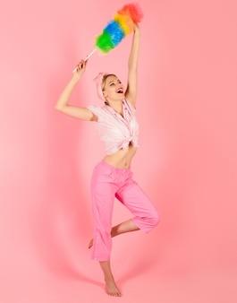 Vrouw met schoonmaakbeurt schoonmaakster gelukkig meisje houdt kleurrijke stofdoekborstel schoonmaakservice