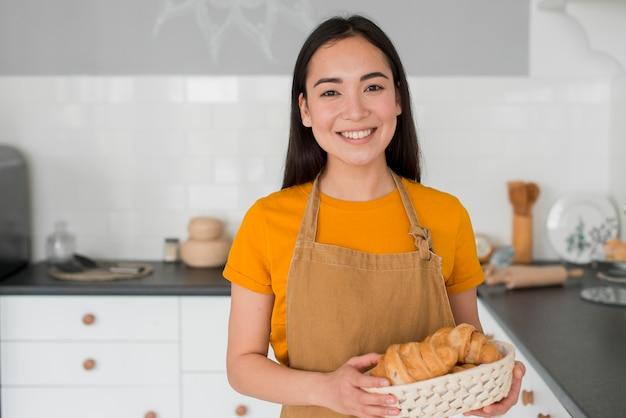 Vrouw met schort met mandje van croissant