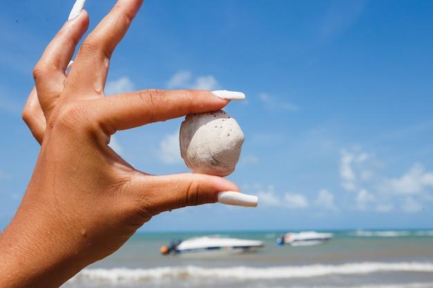 Vrouw met shell in de hand met de oceaan op de achtergrond. strand