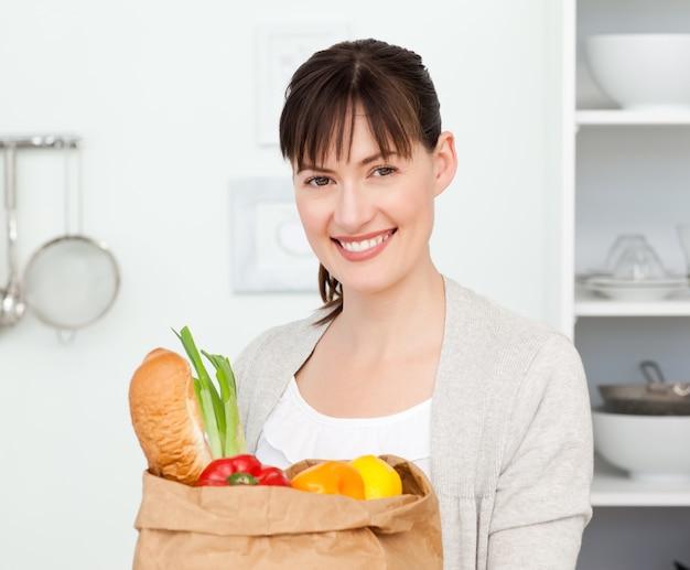 Vrouw met shoping bags in de keuken