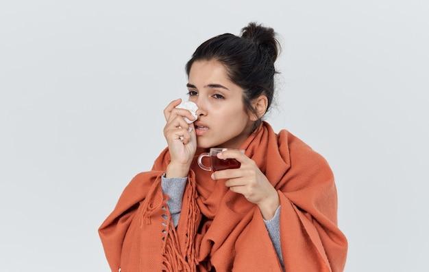 Vrouw met sinaasappel op haar schouders veegt haar neus af met een allergische reactie van een servet.
